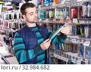 Man customer choosing fishing lures near stand in the sports shop. Стоковое фото, фотограф Яков Филимонов / Фотобанк Лори