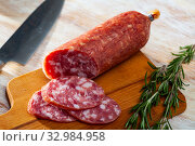 Appetizing salchichon sausage on wooden table. Стоковое фото, фотограф Яков Филимонов / Фотобанк Лори