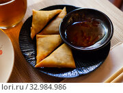 Купить «Potato curry samosas served with sause at plate», фото № 32984986, снято 30 мая 2020 г. (c) Яков Филимонов / Фотобанк Лори
