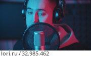Купить «A man in hoodie rapping through the pop-filter in the microphone», видеоролик № 32985462, снято 3 июля 2020 г. (c) Константин Шишкин / Фотобанк Лори