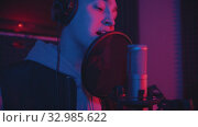Купить «A man in hoodie rapping through the pop-filter in the microphone - sound recording studio», видеоролик № 32985622, снято 4 июля 2020 г. (c) Константин Шишкин / Фотобанк Лори