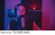 Купить «A man in hoodie rapping through the pop-filter in the microphone - recording his track», видеоролик № 32985642, снято 3 июля 2020 г. (c) Константин Шишкин / Фотобанк Лори