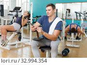 Купить «Man sitting on training apparatus», фото № 32994354, снято 5 ноября 2018 г. (c) Яков Филимонов / Фотобанк Лори
