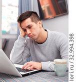 Купить «Upset young man counts family budget on laptop», фото № 32994398, снято 6 августа 2020 г. (c) Яков Филимонов / Фотобанк Лори