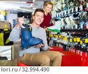 Saleswoman is helping man to trying on boots for skiing. Стоковое фото, фотограф Яков Филимонов / Фотобанк Лори