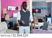 Купить «Portrait of smiling salesman who is offering modern furniture», фото № 32994526, снято 19 февраля 2018 г. (c) Яков Филимонов / Фотобанк Лори