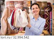 Young woman shopping carpet and showing samples. Стоковое фото, фотограф Яков Филимонов / Фотобанк Лори