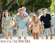 Купить «Adult parents with kids taking fast promenade», фото № 32994582, снято 7 июля 2020 г. (c) Яков Филимонов / Фотобанк Лори