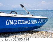 Купить «Спасательная лодка на у линии воды на пляже поселка Кабардинка», фото № 32995194, снято 31 июля 2019 г. (c) Вячеслав Палес / Фотобанк Лори