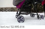 Купить «Mother pushing baby buggy with small wheels on snowy pathway, close up view of female legs stepping on snow», видеоролик № 32995614, снято 21 января 2020 г. (c) Кекяляйнен Андрей / Фотобанк Лори