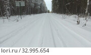 Купить «Winter road in forest covered with snow, wheel tracks with snowdrifts. Camera moving forward», видеоролик № 32995654, снято 20 января 2020 г. (c) Кекяляйнен Андрей / Фотобанк Лори