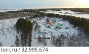 Купить «View from above at Russian village covered with snow, drone flyng in forest of Karelia at sunset in winter season», видеоролик № 32995674, снято 20 января 2020 г. (c) Кекяляйнен Андрей / Фотобанк Лори