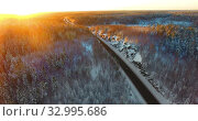 Aerial view from drone at highway passing through mountains at sunset light, northern woods of Karelia. Стоковое видео, видеограф Кекяляйнен Андрей / Фотобанк Лори