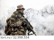 Купить «Elite commando fighter, private military company mercenary, army special forces veteran in camouflage uniform, shemagh and bonnie, equipped radio headset standing with sniper rifle in clouds of smoke.», фото № 32998554, снято 26 ноября 2017 г. (c) easy Fotostock / Фотобанк Лори