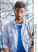 Купить «Electrician trying to untangle wires in repair concept», фото № 32999082, снято 7 июля 2017 г. (c) Elnur / Фотобанк Лори