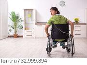 Купить «Young male invalid in wheel-chair suffering at home», фото № 32999894, снято 23 июля 2019 г. (c) Elnur / Фотобанк Лори