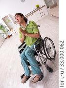 Купить «Young male invalid in wheel-chair suffering at home», фото № 33000062, снято 23 июля 2019 г. (c) Elnur / Фотобанк Лори