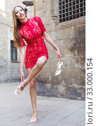 Купить «portrait of slim female in sexually red gown unshoe pumps in the street», фото № 33000154, снято 24 июня 2017 г. (c) Яков Филимонов / Фотобанк Лори