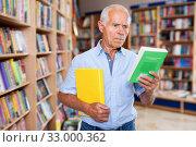 Portrait of intelligent older man choosing necessary books on shelves in library. Стоковое фото, фотограф Яков Филимонов / Фотобанк Лори
