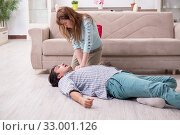 Young couple in first aid concept at home. Стоковое фото, фотограф Elnur / Фотобанк Лори