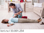 Купить «Young couple in first aid concept at home», фото № 33001254, снято 10 мая 2019 г. (c) Elnur / Фотобанк Лори