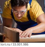 Купить «The worker working in repair workshop in woodworking concept», фото № 33001986, снято 11 августа 2017 г. (c) Elnur / Фотобанк Лори