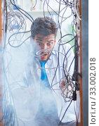 Купить «Electrician trying to untangle wires in repair concept», фото № 33002018, снято 7 июля 2017 г. (c) Elnur / Фотобанк Лори