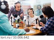 Купить «Multinational group of cheerful young adults emotionally discussing in radio studio», фото № 33006642, снято 16 марта 2019 г. (c) Яков Филимонов / Фотобанк Лори
