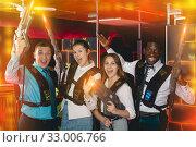 Group of jolly co-workers holding laser guns. Стоковое фото, фотограф Яков Филимонов / Фотобанк Лори