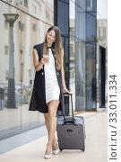 Купить «Stylish businesswoman using smartphone smilingly while walking with suitcase at street.», фото № 33011334, снято 6 августа 2020 г. (c) easy Fotostock / Фотобанк Лори