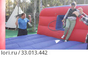 Купить «Two cheerful women having funny battle by big boxing gloves on inflatable arena at amusement park», видеоролик № 33013442, снято 12 ноября 2019 г. (c) Яков Филимонов / Фотобанк Лори