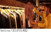 Купить «Young focused woman shopping casual clothes in modern men store», видеоролик № 33013482, снято 7 октября 2019 г. (c) Яков Филимонов / Фотобанк Лори