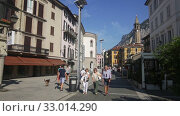 View of busy central street of Italian city of Lecco with gothic bell-tower of Minor Basilica of San Nicolo on background of San Martino mountain in sunny summer day (2019 год). Редакционное видео, видеограф Яков Филимонов / Фотобанк Лори