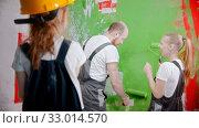 Купить «Parents and daughter are discussing how to paint the wall with green paint», видеоролик № 33014570, снято 3 июня 2020 г. (c) Константин Шишкин / Фотобанк Лори