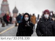 Мужчина и женщина в медицинских масках идут по Красной площади в городе Москве во время эпидемии гриппа, Россия. Редакционное фото, фотограф Николай Винокуров / Фотобанк Лори