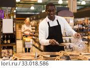 Купить «Man working in bulk food department of supermarket», фото № 33018586, снято 14 ноября 2019 г. (c) Яков Филимонов / Фотобанк Лори