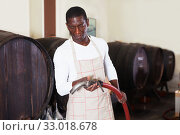 Купить «Wine producer controlling production wine in winery, preparing for wine filtration», фото № 33018678, снято 1 августа 2019 г. (c) Яков Филимонов / Фотобанк Лори