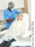 Cosmetologist man in mask preparing woman client for mesotherapy procedure. Стоковое фото, фотограф Яков Филимонов / Фотобанк Лори