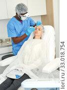 Cosmetologist man in mask preparing woman client for mesotherapy procedure. Стоковое фото, фотограф Яков Филимонов / Фотобанк Лори