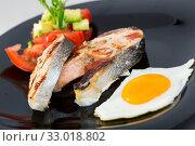 Купить «Fried salmon on black plate with fried egg, tomatoes, avocado», фото № 33018802, снято 26 февраля 2020 г. (c) Яков Филимонов / Фотобанк Лори