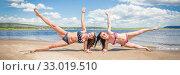 Купить «Two young beautiful women doing gymnastics in their arms on the beach on a sunny summer day.», фото № 33019510, снято 7 июля 2019 г. (c) Акиньшин Владимир / Фотобанк Лори