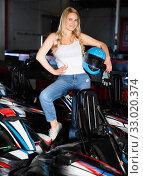 Купить «Smiling woman with helmet standing near cars for motor racing in sport club», фото № 33020374, снято 31 мая 2020 г. (c) Яков Филимонов / Фотобанк Лори
