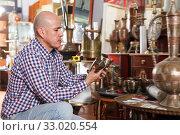 Купить «Smiling male carefully examining antiques», фото № 33020554, снято 15 мая 2018 г. (c) Яков Филимонов / Фотобанк Лори
