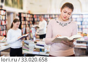 Купить «Young woman browsing inside of books while visiting public libra», фото № 33020658, снято 22 февраля 2018 г. (c) Яков Филимонов / Фотобанк Лори