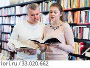 Купить «Cheerful couple choosing and discussing books», фото № 33020662, снято 22 февраля 2018 г. (c) Яков Филимонов / Фотобанк Лори