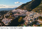 Aerial photo distant view charming Mijas pueblo, typical Andalusian white-washed mountain village, houses rooftops, small town located on hillside Province of Málaga, Costa del Sol, Europe, Spain (2019 год). Стоковое фото, фотограф Alexander Tihonovs / Фотобанк Лори