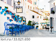 Mijas Pueblo Blanco, charming small village, picturesque empty street in old town with bright blue tables chairs of local cafe, flower pots hanging on white washed houses walls, Costa del Sol, Spain. Стоковое фото, фотограф Alexander Tihonovs / Фотобанк Лори
