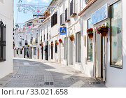 Mijas white washed street, small famous village in Spain. Charming empty narrow streets with New Year decorations, on houses walls hanging flower pots, sunny day no people. Costa del Sol, Málaga (2019 год). Стоковое фото, фотограф Alexander Tihonovs / Фотобанк Лори