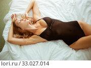 Купить «Beautiful sexy slim girl with a perfect figure lies on a white sheet in black bodysuit», фото № 33027014, снято 9 сентября 2017 г. (c) katalinks / Фотобанк Лори