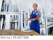 Confident man in workwear with finished window from pvc profile at workplace. Стоковое фото, фотограф Яков Филимонов / Фотобанк Лори